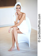 Woman Wearing White Bath Towel Sitting on Chair with Legs...