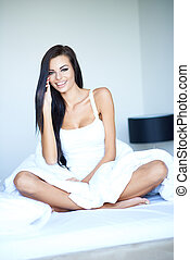 Beautiful smiling woman sitting on her bed - Beautiful...