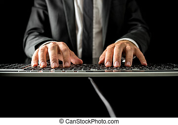 Man typing on a computer keyboard - Low angle frontal view...