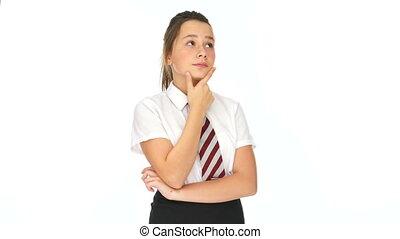 Young schoolgirl deep in thought standing in her uniform...