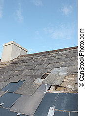 damaged home roof - hole in a roof due to storm or decay