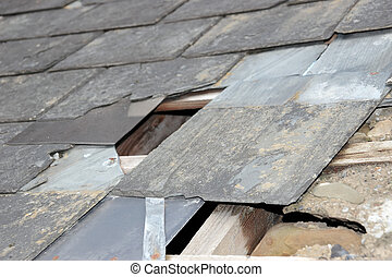 damaged slated roof - hole in a roof due to storm or decay