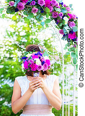 Bridesmaid with a wedding bouquet. Arch for wedding ceremony...