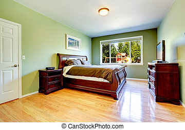 Green bedroom with carved wood furniture