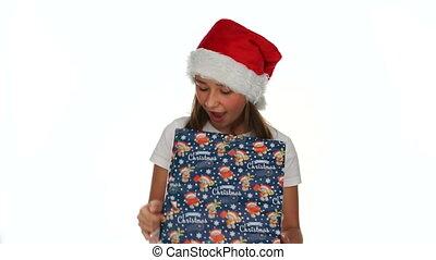 Little girl tearing open a Christmas present - Little girl...