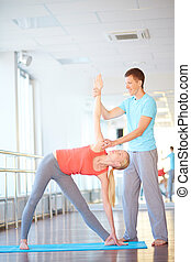 Exercising with trainer - Young woman doing physical...