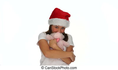 Young girl in a Santa Hat kissing a teddy bear in her...