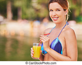 Charming girl - Young woman in bikini with juice looking at...