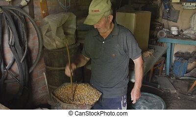 grinding corn - Elderly man grinds corn Pensioner prepares...