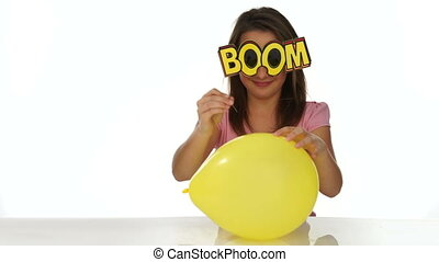 Young girl getting ready to burst a party balloon - Playful...