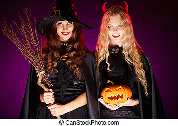 Halloween celebrators - Two young women with broom and...