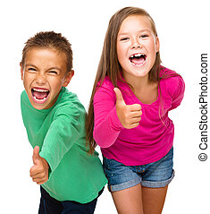 Little boy and girl are showing thumb up sign, isolated over...