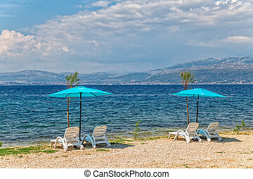 Beach in Supetar on island Brac - Four deck chairs and two...