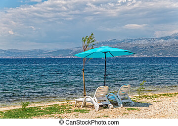 Beach in Supetar on island Brac - Two deck chairs and blue...