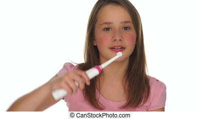 Responsible young girl brushing her teeth with an electric...