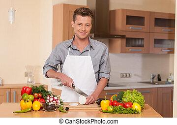 handsome man cutting onion on chopping board. guy preparing...