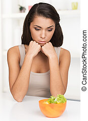upset young woman keeping diet and eating vegetables. Sad...