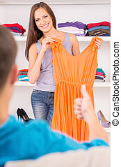 Woman trying new dresses on and smiling. man sitting in...