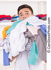 young smiling man holding laundry. portrait of young man...
