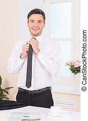 Close-up of businessman adjusting neck tie. waist up of...