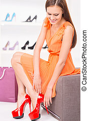 Woman trying red shoes sitting in a shop Young woman in...