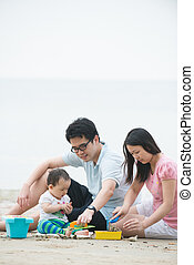 asian family playing on a beach during sunset