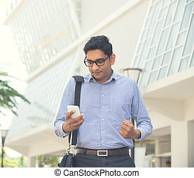 happy young indian business man on a smartphone light...