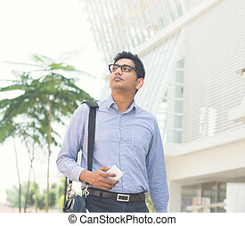 young indian business man on a smartphone light vintage tone