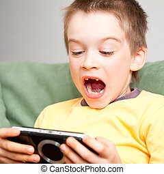 Boy playing game console - Young boy playing handheld game...