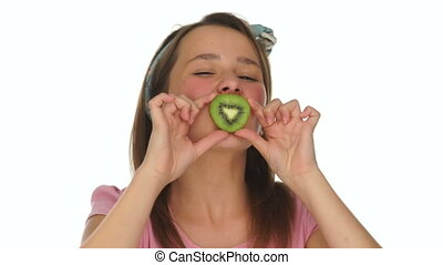 Young girl biting on a slice of fresh kiwifruit with a smile...