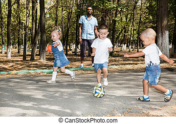 Group of happy children playing with soccer ball in park on...