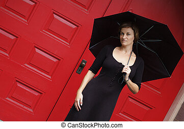 Woman With Umbrella - Woman with umbrella in front of red...