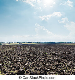 sun in clouds over black field after harvesting