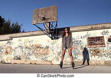 girl with roller skates on graffiti background and a...