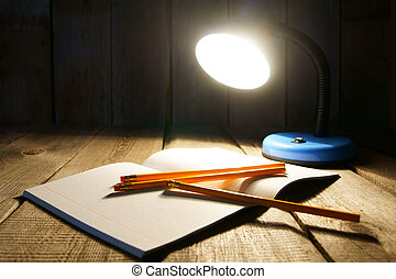 Open writing-book and the fixture. On a wooden background.