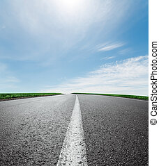 asphalt road to horizon under sky with clouds and sun