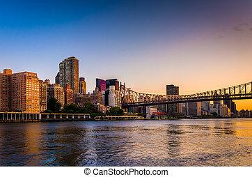 The Queensboro Bridge and Manhattan skyline at sunrise, seen fro