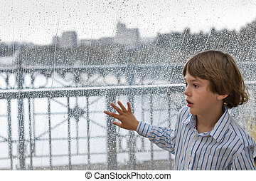 Cute boy standing next to a wet window on a rainy day