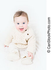 Funny baby sitting on a white bed in a warm cable knit...