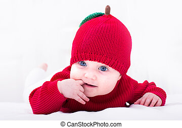 Funny baby girl in a red apple hat