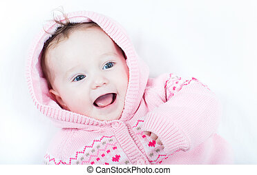 Laughing baby girl wearing a knitted pink sweater with red...