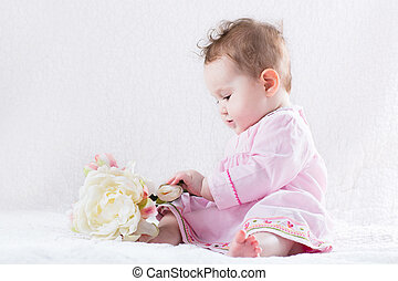 Adorable baby girl playing with a big white flower