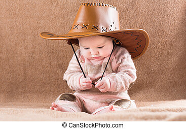 Funny baby in a big cowboy hat