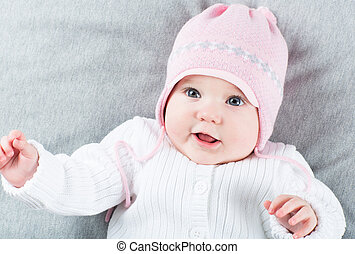 Sweet baby girl on a grey blanket wearing a pink hat