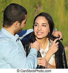 Happy arab couple flirting while man cover her with his...