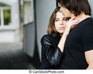 Young couple holding each other in the city