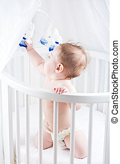 Little baby playing in a white nursery