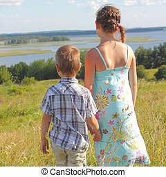 Brother and sister in a landscape. View from the back
