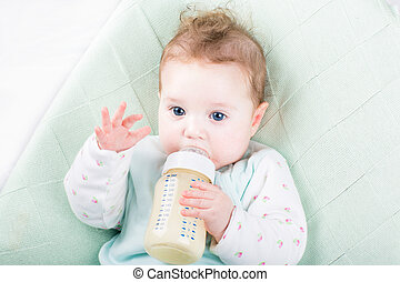 Adorable baby girl on a green knitted blanket drinking milk