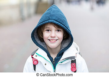 Happy school boy walking on a street with a backpack on a cold day